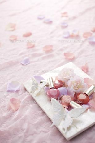 ピンクのレースの上に白いフォトスタンドとマニキュアと花びらの素材 [FYI00961137]
