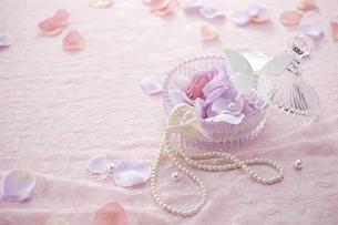 ピンクのレースの上にガラスの器とパールのネックレスと花びらの素材 [FYI00961169]