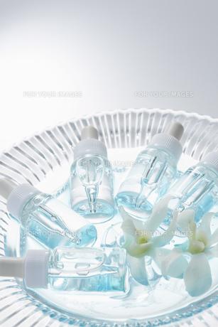 ガラスの器に転がる数本のガラスビンと白い花の素材 [FYI00961309]