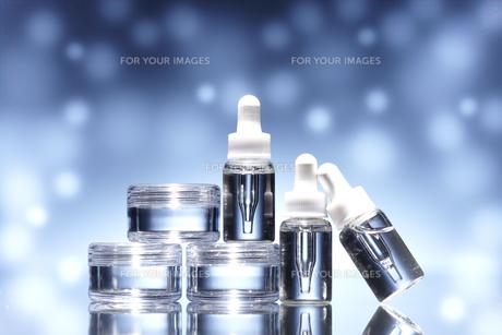 青く輝く背景に色々な形のコスメのボトルの素材 [FYI00961333]