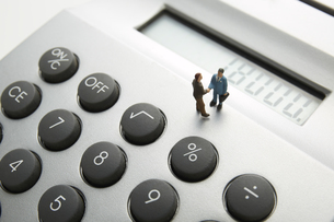 電卓の上で握手をする人形の素材 [FYI00961535]