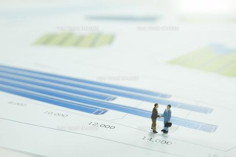 棒グラフの上に立つ2個のサラリーマンの人形の素材 [FYI00961539]
