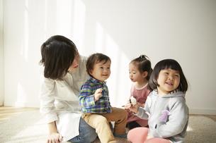 お母さんの膝に座る男の子と二人の女の子の素材 [FYI00962376]