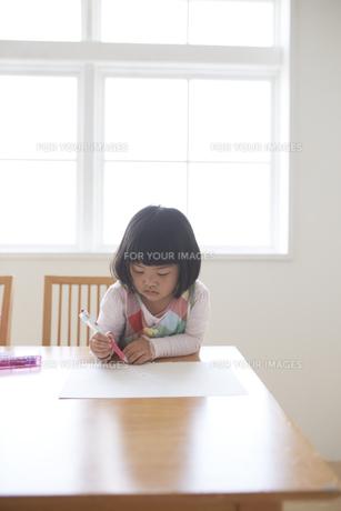 窓辺でお絵かきをする女の子の素材 [FYI00962552]