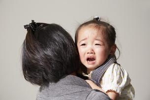 お母さんに抱いてもらう泣き顔の女の子の素材 [FYI00962595]