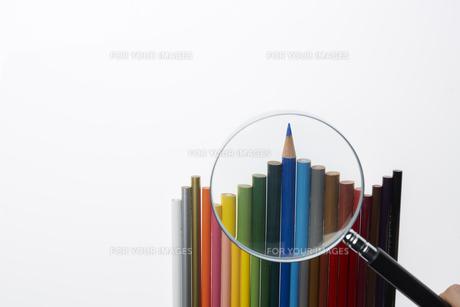 波のように並ぶカラフルなイロ鉛筆と虫眼鏡の素材 [FYI00962740]