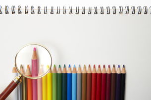 画用紙の上に並べられたイロ鉛筆と虫眼鏡の素材 [FYI00962754]