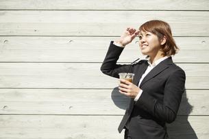 コーヒーを片手に日差しをもう片方の手で避けるスーツ姿の女性の素材 [FYI00962759]