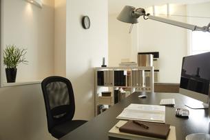 白い部屋の机と本棚机のうえに書類とパソコンの素材 [FYI00962766]