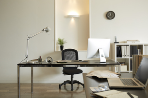 白い部屋の二つの机と本棚机のうえに書類とパソコンの素材 [FYI00962780]