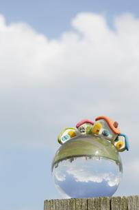 ガラス球の上の粘土の家と空の素材 [FYI00962785]