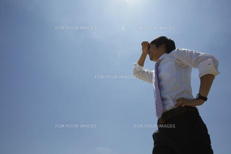 青空の下で額の汗を拭うビジネスマンの素材 [FYI00962800]