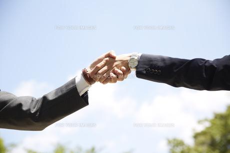 青空の下で握手をする男性の手元スーツの素材 [FYI00962805]