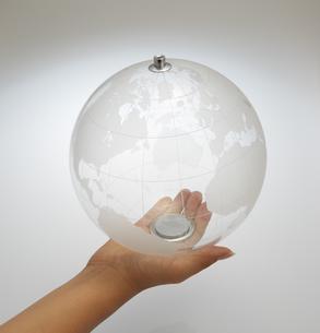 透明な地球儀を持つ女性の手の素材 [FYI00962831]