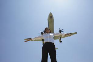 青空と飛行機をバックに両手を広げる白いブラウスの女性の素材 [FYI00962836]