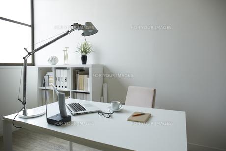 白い部屋の白い家具の机と本棚机の上にはコーヒーとメガネとノートパソコンの素材 [FYI00962843]