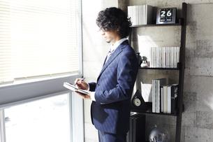 窓辺に立ち手帳に書くビジネスマンの素材 [FYI00962850]