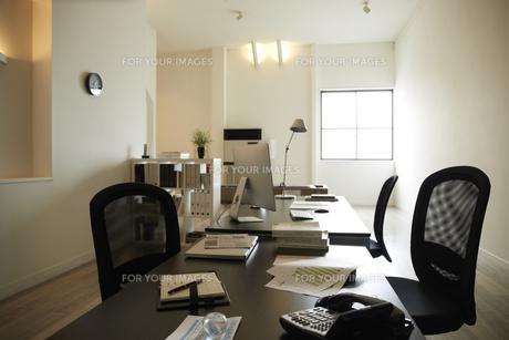 白い部屋の窓辺に置かれた二つの机と本棚机のうえに書類とパソコンの素材 [FYI00962862]