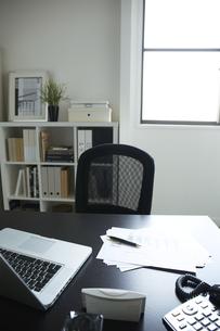 白い部屋の窓辺に置かれた机と本棚机のうえに書類とパソコンの素材 [FYI00962874]