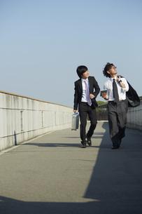 青空を見上げながら歩く2人のビジネスマンの素材 [FYI00962879]