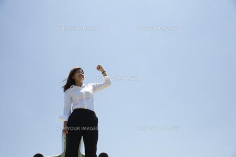 青空をバックにガッツポーズをしている白いブラウスの女性の素材 [FYI00962880]
