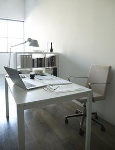 白い部屋の窓辺に置かれた白い机と本棚机のうえに書類とパソコンとコーヒーの素材 [FYI00962881]