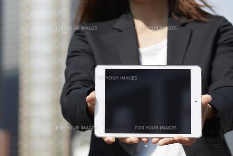 ビルを背景にタブレット端末を持つスーツの女性の素材 [FYI00962886]