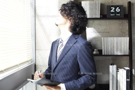 窓辺に立ち手帳に書くビジネスマンの素材 [FYI00962893]