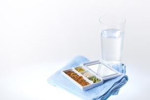 ケースに入った各種ビタミン剤とタオルとグラスの素材 [FYI00962901]
