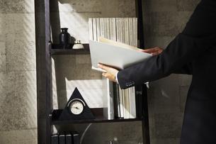 本棚の前でファイルを広げているビジネスマンの手元の素材 [FYI00962913]