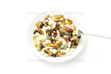 お皿のビタミン剤をスプーンですくうの素材 [FYI00962924]