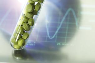 モニターの上のビタミン錠剤の入った試験管の素材 [FYI00962972]