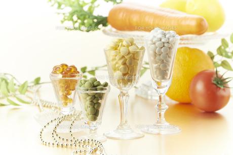 グラスに入ってる各種ビタミン剤と野菜の素材 [FYI00962978]