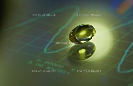 モニターの上のビタミンカプセルの素材 [FYI00963057]