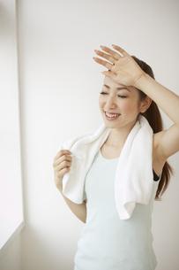 タオルを首にかけ手で額の汗を拭く女性の素材 [FYI00963074]