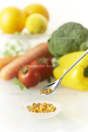 野菜と器のビタミンカプセルをスプーンですくうの素材 [FYI00963113]