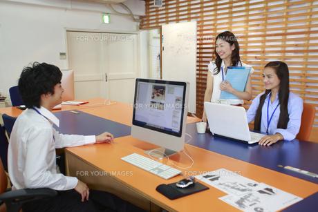 シェアオフィスのデスクで話す3人の男女ビジネスウーマンの素材 [FYI00965395]