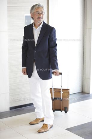 旅行鞄を持ったミドル男性のポートレートの素材 [FYI00965481]