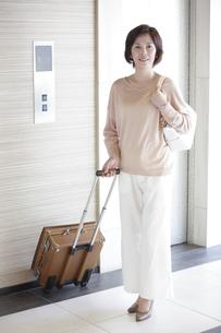 旅行鞄を持ったミドル女性のポートレートの素材 [FYI00965494]