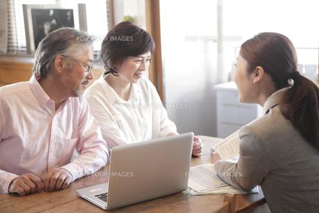 自宅でビジネスウーマンの説明を聞くミドル夫婦の素材 [FYI00965573]