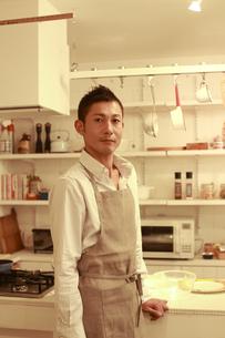 夜のキッチン前での30代男性ポートレートの素材 [FYI00965656]