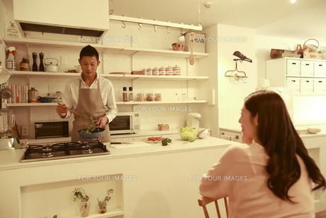 夕食を調理する夫とそれを見る後姿の女性の素材 [FYI00965681]