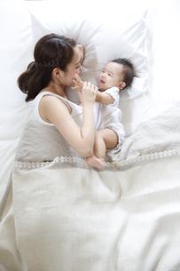 ベッドで赤ちゃんをあやす若い母親の素材 [FYI00967233]