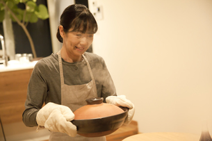 鍋を運ぶミドル女性の素材 [FYI00968026]