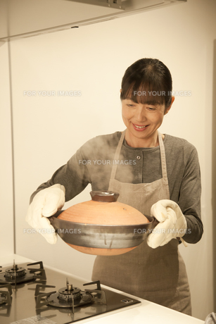 鍋を運ぶミドル女性の素材 [FYI00968220]