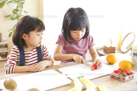 果物をカットする幼い姉妹の素材 [FYI00968499]