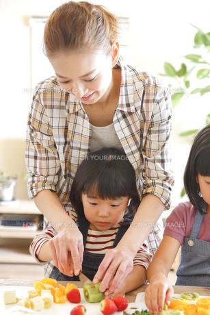 母親と果物をカットする幼い姉妹の素材 [FYI00968565]