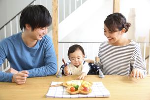 赤ちゃんにごはんを食べさせる若いカップルの素材 [FYI00968601]