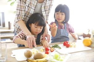 母親と果物をカットする幼い姉妹の素材 [FYI00968620]
