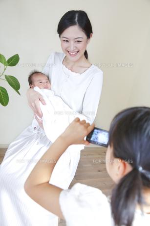 赤ちゃんを抱いた母親を撮影する女の子の素材 [FYI00968649]